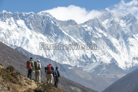 trekkers look up at everest the