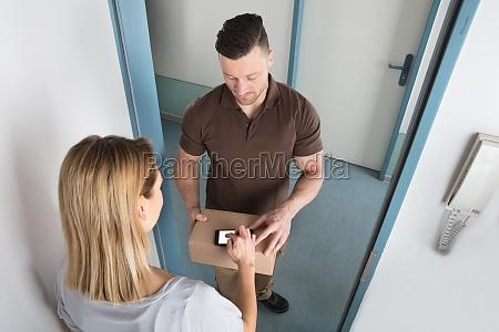 mloda kobieta podpisywanie po otrzymaniu dostawy
