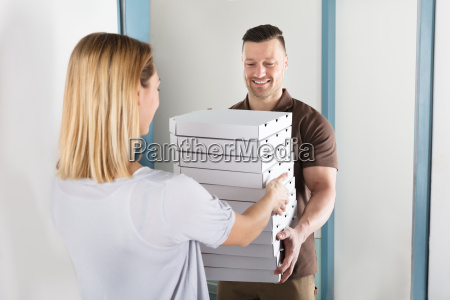 man delivering stack of pizza
