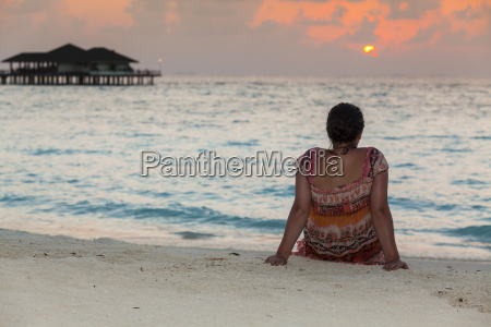 maldives teenage girl sitting at beach