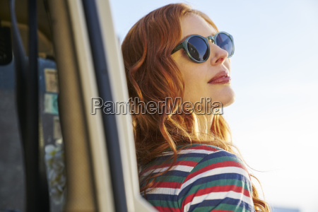 young woman wearing sunglasses leaning against