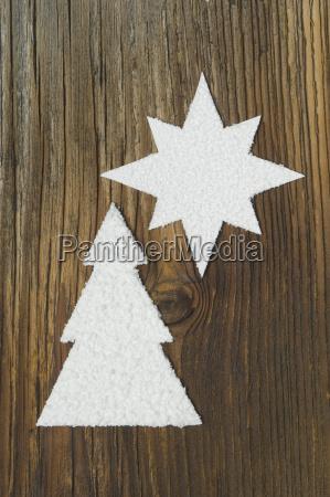 geschnitzter weihnachtsbaum und stern auf holzbrett