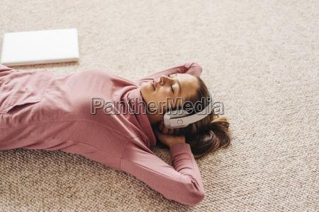 frau liegt mit kopfhoerer auf teppich