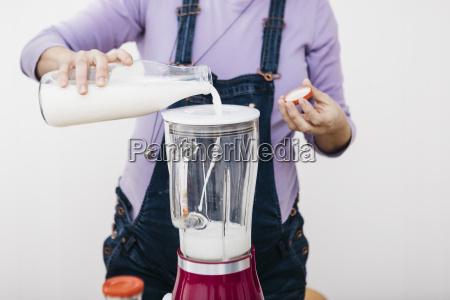 pregnant woman pouring milk into a