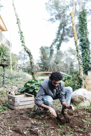 mann der in seinem garten pflanzt