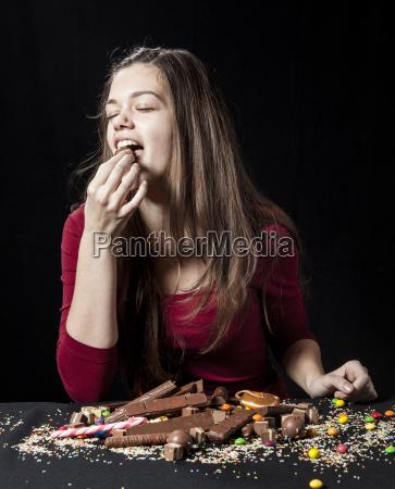 teenage girl eating a chocolate ball