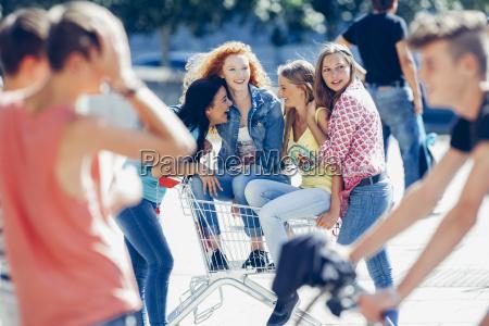 vier freundinnen mit einkaufswagen verbringen ihre