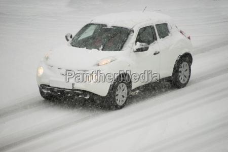 deutschland weisses auto faehrt auf schneebedeckter