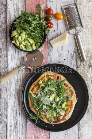 vegetarian pizza with avocado rocket tomatoes