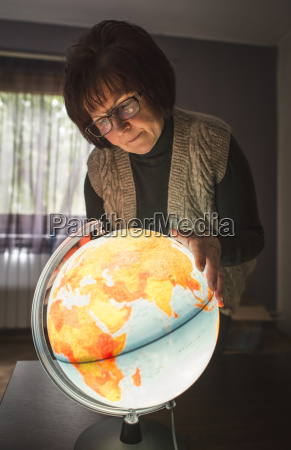 senior woman looking at lighted globe