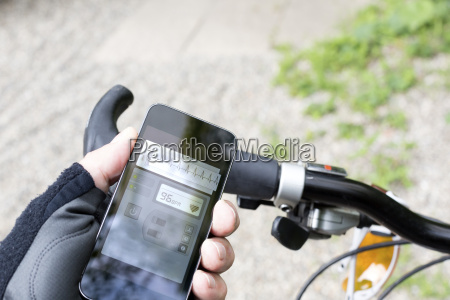 hand of mountain biker holding smartphone