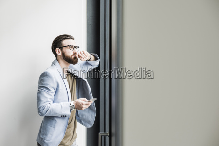 young businessman standing in office using