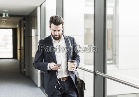 businessman walking in office building while