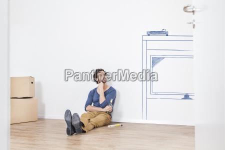 mann denkt ueber einrichtung neuer wohnzimmer