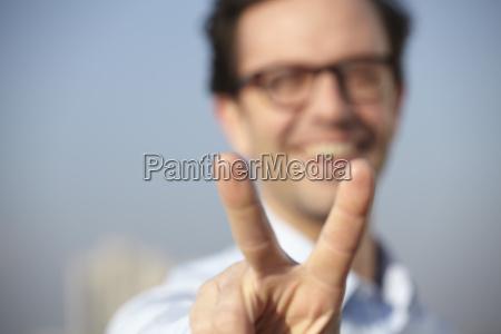 portraet des laechelnden mannes zeigt sieg