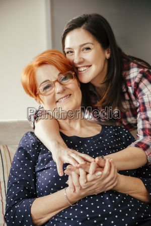 happy adult daughter embracing mother