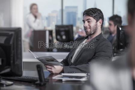 smiling man looking at booklet at