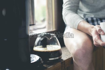mann sitzt neben kaffeekanne auf fensterbank