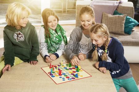 vier kinder spielen ludo im wohnzimmer