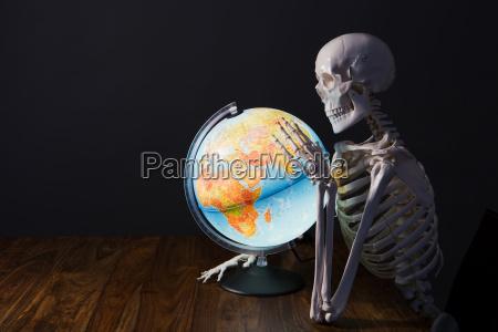 skeleton holding globus