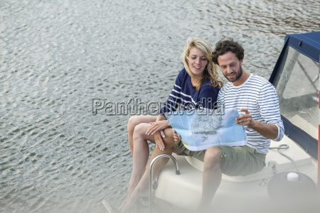 couple on boat looking at map