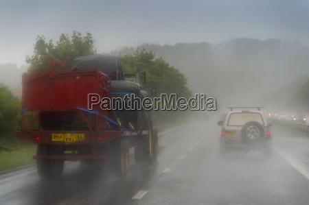 traktor mit anhaenger auf der autobahn
