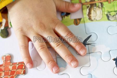 hand of little girl doing jigsaw