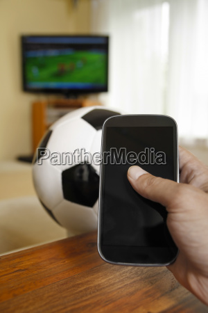 mature man holding mobile with soccer