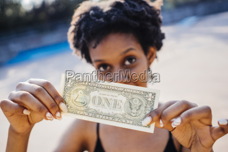 woman showing one dollar banknote close