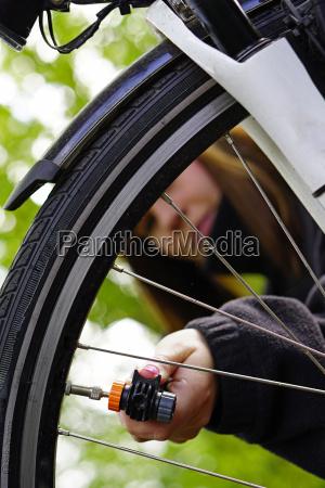frau die fahrradreifen auffuellt