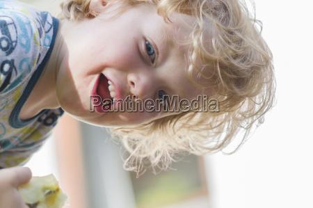 austria portrait of boy eating apple