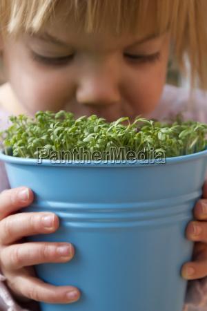 girl holding blue pot with garden