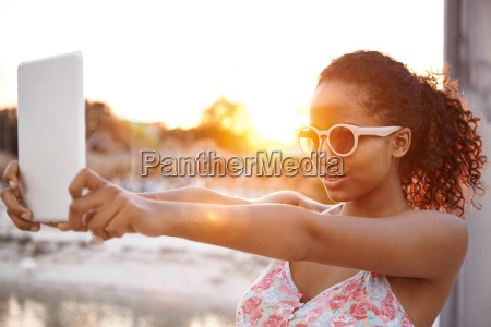 young woman taking selfie with digital