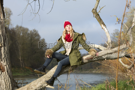 young woman sitting at tree trunk