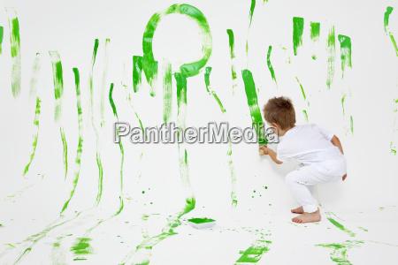 kleinkind hat spass mit gruener farbe