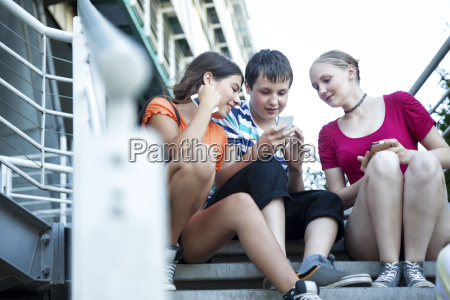 teenage friends using mobile devices on