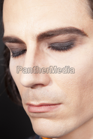 man with make up eyes closed