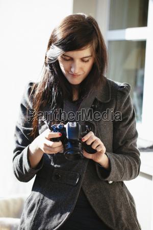 junge frau schaut auf ihre digitalkamera