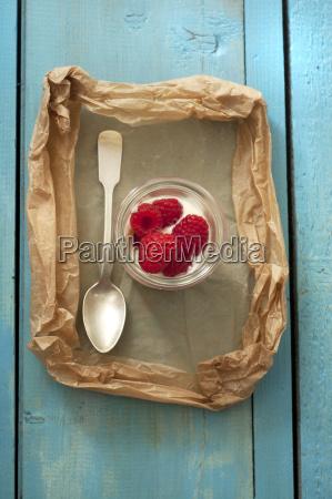 glas joghurt mit himbeeren auf holztisch