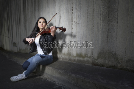 young female asian playing violin in