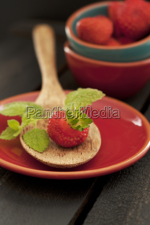 strawberry on wooden spoon close up