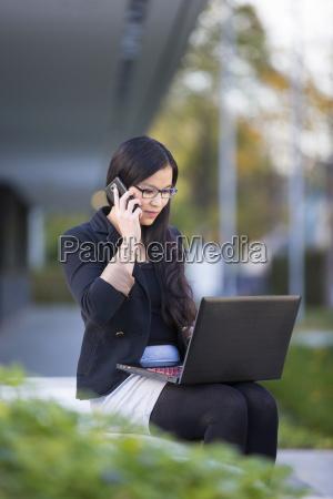 junge geschaeftsfrau mit laptop telefonieren mit