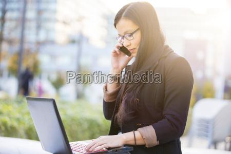 junge geschaeftsfrau mit dem laptop der