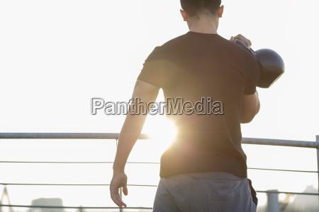man training with kettlebell at backlight