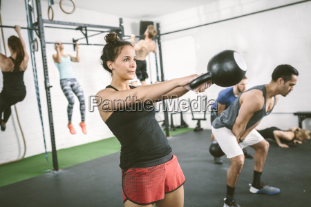 people in gym training with kettle