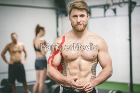 young muscular man in gym with