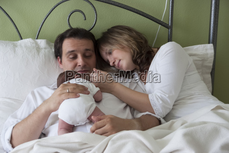 parents with newborn baby girl lying