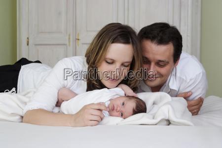 eltern mit neugeborenem baby liegen auf