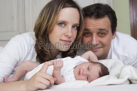portraet der eltern mit neugeborenem maedchen