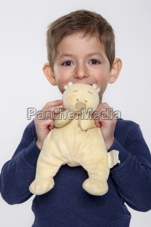 portrait of boy holding toy close